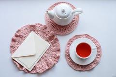 Tazza di tè rosa profumato sul tovagliolo, sulla teiera e sulla busta di lavoro all'uncinetto sul davanzale Rosa rossa Buongiorno immagine stock libera da diritti