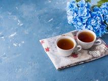 Tazza di tè su fondo blu con i fiori Fotografia Stock Libera da Diritti