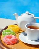 Tazza di tè su una salsa, su una teiera e su una marmellata d'arance colorata immagine stock