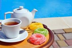 Tazza di tè su una salsa, su una teiera e su una marmellata d'arance colorata fotografia stock