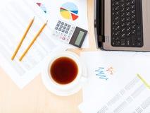 Tazza di tè sulla tavola con gli strumenti in ufficio moderno Immagine Stock