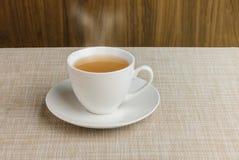 Tazza di tè sulla tovaglia e sul fondo di legno Fotografie Stock Libere da Diritti