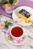 Tazza di tè con torta di formaggio ed il fiore rosa selvaggio su vecchio fondo di legno Fotografia Stock Libera da Diritti