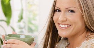 Tazza di tè felice della holding della donna Immagine Stock