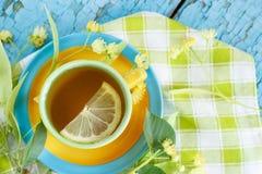 Tazza di tisana con i fiori ed il limone del tiglio Fotografia Stock