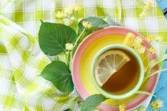 Tazza di tisana con i fiori ed il limone del tiglio Fotografia Stock Libera da Diritti