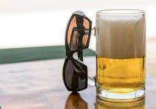 Tazza di vetro di birra dorata con alta schiuma bianca e degli occhiali da sole su una tavola Immagini Stock Libere da Diritti