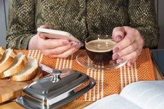 Tazza di vetro con caffè nero ed il telefono in mani femminili con il manicure Fotografia Stock Libera da Diritti