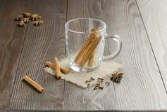 Tazza di vetro con i bastoni di cannella Immagine Stock