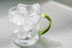 Tazza di vetro con i cubetti di ghiaccio Fotografie Stock Libere da Diritti