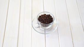 Tazza di vetro con i fagioli del coffe sulla tavola bianca archivi video