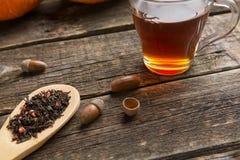 tazza di vetro con tè e la cucchiaiata di legno della tisana della bacca fotografia stock
