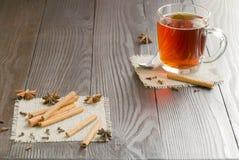 Tazza di vetro dei bastoni di cannella e del tè Immagine Stock