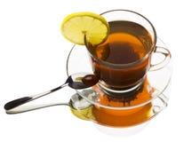 Tazza di vetro di tè con il limone su un fondo bianco Immagine Stock