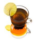 Tazza di vetro di tè con il limone su un fondo bianco Fotografia Stock