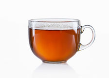 Tazza di vetro di tè nero su fondo bianco Immagini Stock