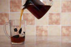Tazza di vetro di vetro e della teiera con tè sulla tavola Immagini Stock