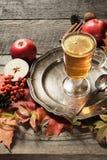 Tazza di vetro di riscaldamento di tè con una decorazione delle foglie e delle mele di autunno su un bordo d'annata di legno Cadu Fotografie Stock