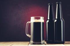 Tazza e bottiglie sullo scaffale di legno su un fondo rosso/su una tazza birra scura e bottiglie di birra scura sullo scaffale di fotografia stock