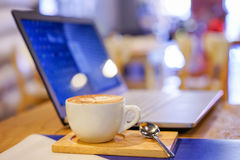 Tazza e computer portatile di caffè per l'affare, fuoco selettivo su caffè fotografia stock
