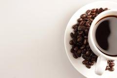 Tazza e fagioli di caffè su priorità bassa bianca Fotografia Stock Libera da Diritti