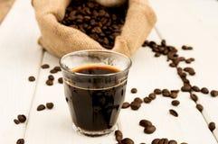 Tazza e fagioli di caffè su una priorità bassa bianca Fotografia Stock Libera da Diritti
