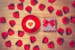 Tazza e petali con il contenitore di regalo Fotografie Stock Libere da Diritti
