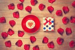 Tazza e petali con il contenitore di regalo Immagine Stock