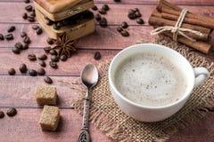 Tazza e piattino di caffè macchiato con i fagioli di Anise Coffee della cannella dello zucchero della schiuma e di canna del latt immagini stock libere da diritti