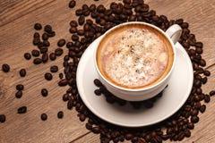 Tazza e piattino di caffè su una tabella di legno con Fotografie Stock Libere da Diritti