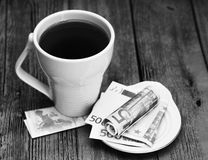 Tazza e soldi bianchi dell'euro, bella mattina romantica fotografie stock