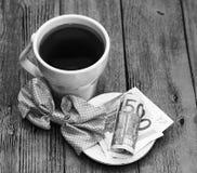 Tazza e soldi bianchi dell'euro, bella mattina romantica fotografia stock libera da diritti