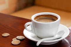 Tazza e soldi di caffè sulla tabella Immagini Stock