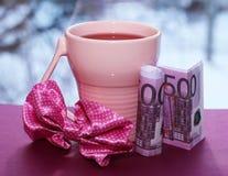Tazza e soldi rosa, bella mattina romantica immagini stock