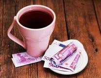 Tazza e soldi rosa, bella mattina romantica immagine stock