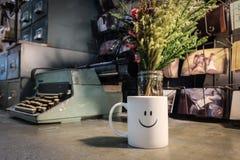 Tazza felice sorridente della tazza di caffè sulla tavola del metallo Immagine Stock