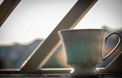 Tazza fotografata sopra la finestra aperta, backlit Fotografie Stock