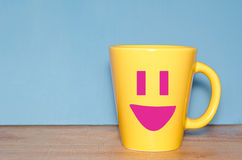 Tazza gialla con il fronte felice Fotografia Stock Libera da Diritti