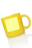 Tazza gialla con l'autoadesivo della nota Fotografie Stock