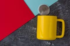 Tazza gialla su fondo di pietra nero Carta rossa e blu della bustina di t?, dei biscotti, Con lo spazio della copia immagini stock
