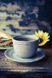 Tazza grigia di tè su una tavola di legno contro lo sfondo delle baguette e di un girasole immagine stock