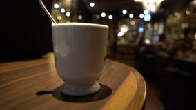 tazza 4K di latte sulla tavola nella barra delle cene del caffè della caffetteria nel Giappone alla sera stock footage
