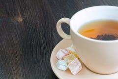 Tazza leggera di tè e dolci orientali sul piattino Fotografie Stock