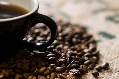 Tazza nera con la maniglia, su un sacco del caffè con il aroun dei semi di cacao torrefatti Immagini Stock Libere da Diritti