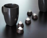 Tazza nera con le caramelle di cioccolato Fotografie Stock Libere da Diritti