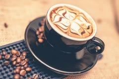 Tazza nera del caffè di recente preparato del caffè espresso Primo piano della tazza di caffè con latte ed i fagioli Fotografia Stock Libera da Diritti