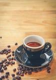 Tazza nera di caffè espresso con i chicchi di caffè rovesciati sulla tavola di legno Fotografia Stock