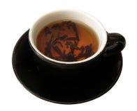 Tazza nera di tè sopra priorità bassa bianca fotografie stock libere da diritti