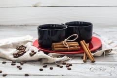 Tazza nera, fondo di legno, bevanda, mattina di natale, chicchi di caffè, bastoni di cannella fotografia stock