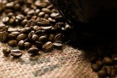 Tazza nera sopra di un sacco del caffè con i semi di cacao torrefatti intorno Fotografie Stock